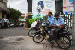 Two Men Sitting on Motorbikes At A Sidewalk Stock Images