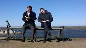 Two men sitting outdoors on a bench with a book. Professional shot on BMCC with high dynamic range. You can use it e.g in your commercial video, business or stock footage