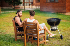 Two men sitting while preparing barbecue grill in park zone Stock Photo