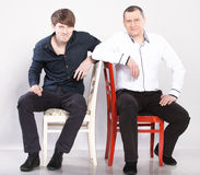 Two men sitting on red and white chair Royalty Free Stock Photography