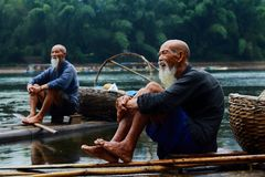 Two Men Sitting on Riverbank Royalty Free Stock Image