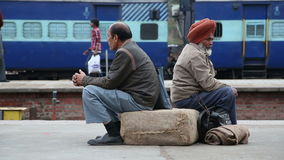 Two men sitting on sack and waiting at train station in Amritsar. AMRITSAR, INDIA - 2 MARCH 2015: Two men sitting on sack and waiting at train station in stock video footage