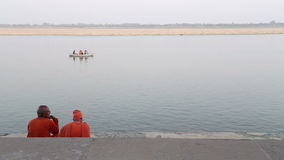Two men sitting on stairs and watching boat sailing on Ganges river. stock video footage