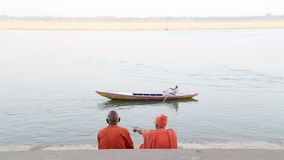 Two men sitting on stairs and watching boat sailing on Ganges river. stock footage