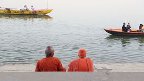 Two men sitting on stairs and watching boats sailing on Ganges river. stock footage