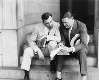 Two men sitting on steps and reading a document. (All persons depicted are no longer living and no estate exists. Supplier grants that there will be no model royalty free stock photo