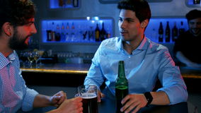 Two men sitting at a table in bar. Two men sitting at a table and talking in bar 4K stock footage