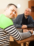 Two men sitting at table. Man sitting at table at home and talking with another man royalty free stock photos