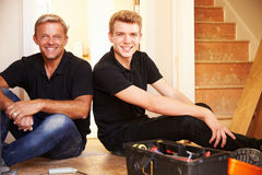 Two men sitting on wooden floor during a house refurbishment Stock Images