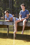 Two Men Sitting On Wooden Jetty Looking Out Over Lake Stock Photo