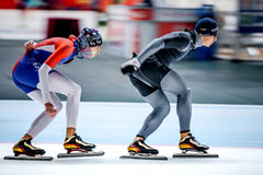 Two men skaters race behind other Stock Photo