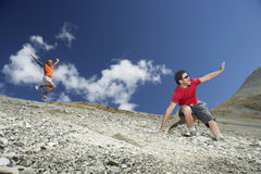 Two Men Sliding Down Scree Field Stock Photography