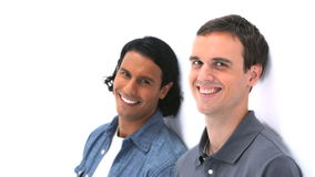 Two men smiling while leaning against a wall stock footage