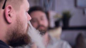 Two men smoking electronic smoking electronic cigarette. Smoke, fume. stock video