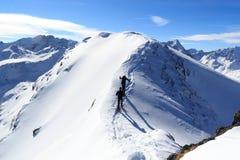 Two men snowshoe hiking on mountain snow arete and panorama in Stubai Alps. Austria Royalty Free Stock Photos