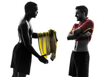 Two men soccer player  exchanging jersey standing silhouette Royalty Free Stock Image