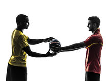 Two men soccer player giving football silhouette stock photos