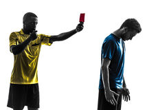 Two men soccer player and referee showing red card silhouette Royalty Free Stock Images