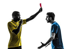 Two men soccer player and referee showing red card silhouette Stock Image