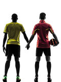 Two men soccer player  standing hand in hand silhouette Stock Image