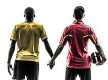 Two men soccer player  standing holding hands silhouette Stock Photo