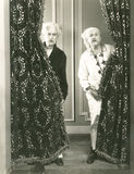 Two men spying from behind drapes Stock Images
