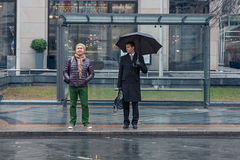 Two men stand at the bus stop, one of them is sad, another is ch. Eerful, it`s raining, one of them with an umbrella Royalty Free Stock Photo