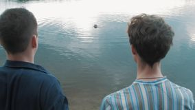 Two men stand shore looking at coming out water scooba diver stock video footage
