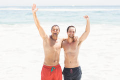 Two men standing beach with hands raised Royalty Free Stock Images