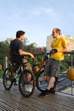 Two men standing on bridge near bicycles Stock Images
