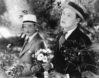 Two men standing in a garden holding a bouquet of flowers Stock Images