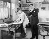 Two men standing in an office, one ironing his pants Royalty Free Stock Image
