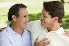 Two men standing outdoors bonding and smiling Stock Image