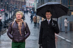Two men are standing on the street, one of them is sad, the othe. Two men are standing on the street thinking, one of them is sad, another is cheerful Stock Photos