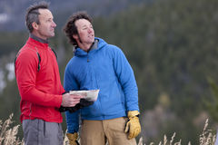 Two Men Standing in the Wilderness With a Map. Two men stand together in a clearing in the wilderness and look out into the distance. One is holding a map Stock Photography