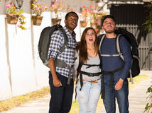 Two men standing with woman in middle, all wearing casual clothing and backpacks, staring up in awe of something Stock Image