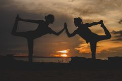 Two men stay in balance while doing yoga postures stock photo