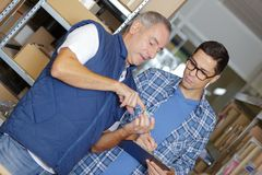 Two men in stores looking at object held in palm hand Royalty Free Stock Photos