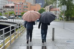 Two men on the street with umbrellas in the rain. Image of two men on the street with umbrellas in the rain Stock Photo