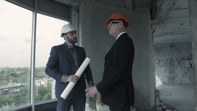 Two men in suit and helmet discuss blueprint, calculate and communicate with colleague. American. Man, designer, show plan to chief engineer builder indoor stock video footage