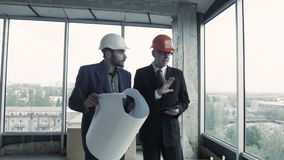 Two men in suit and helmet discuss blueprint, calculate and communicate with colleague. American. Man, designer, show plan to chief engineer builder indoor stock video