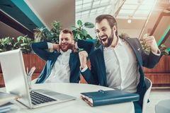 Two men celebrating looking on laptop in office. Stock Photo