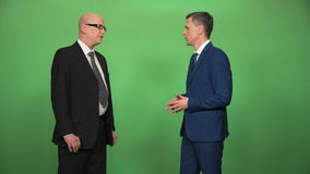 Two men in suits greeting and talking. Two businessman wearing formal suits greeting each other and having conversation isolated on green screen then turn to stock video footage