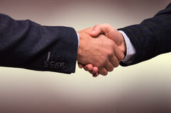 Two men in suits shaking hands stock photos