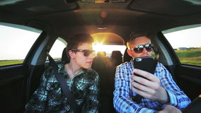Two men in sunglasses driving in the car, using phone in the sunny day stock footage