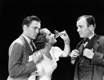 Two men supporting a woman drinking royalty free stock image