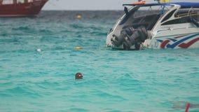 Two men swimming near speedboat. PHAN NGA, THAILAND - NOVEMBER 23, 2015: Two men swimming near speedboat on the beach of Koh Miang, Similan Islands stock video footage