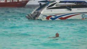 Two men swimming near speedboat. PHAN NGA, THAILAND - NOVEMBER 23, 2015: Two men swimming near speedboat on the beach of Koh Miang, Similan Islands stock footage