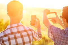 Two men take pictures of the sunset on the phone in the sun stock images