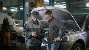 Two men are talking in auto repair shop. Two serious men are discussing price of car maintanence in a garage. Mechanic is counting the cost of repair for client stock video